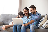 Happy family with kid daughter enjoy using laptop at home