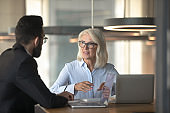 Mature businesswoman talking with business partner in office