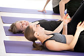 Toned young women laughing during fitness training in gym