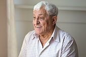 Elderly man looking out the window enjoy sunny day