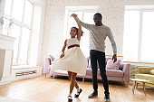 African American dad dancing with small daughter at home