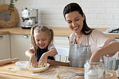 Little daughter helping smiling mother to kneading dough in kitchen