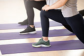 Close up of fit women stretching in fitness studio