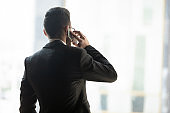 Rear view confident businessman talking on phone with business partner