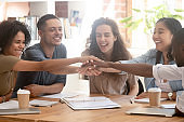 Happy multiracial business people colleagues stacking hands motivated by success
