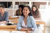 Smiling smart asian student looking at camera sitting at desk