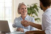 Smiling mature saleswoman handshake businessman client customer at business meeting