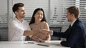 Male broker handshake happy couple congratulate with deal
