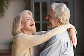 Close up image happy elderly spouses embracing standing indoors