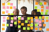 Three happy diverse colleagues team write ideas on sticky notes