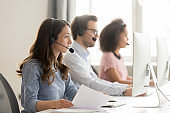 Call center worker holding paper talking with client use headset