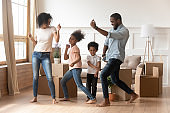Happy african american parents and children dancing celebrating moving day