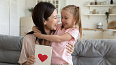 Cheerful mom embracing kid daughter holding postcard with red heart