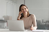 Smiling businesswoman talking on phone making business call at work