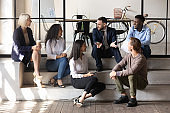 Happy multiracial business people communicating sit on modern office floor