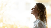 Calm happy business woman breathing fresh air stand at window