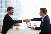 Satisfied happy businessmen shake hands at business office meeting