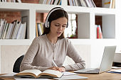 Focused girl in Bluetooth headphones studying at home