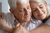 Elderly woman and man closed eyes embracing closeup view faces