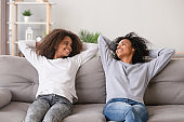 Positive black mother and daughter resting on couch at home