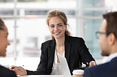 Smiling female employee listen to colleague discussion at meeting