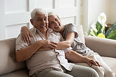 Happy mature couple resting on couch looking at camera