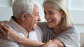 Close up faces elderly wife and senior husband embracing indoors
