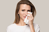 Unhappy depressed young woman crying, wiping tears, personal problem