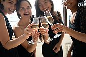 Attractive happy young ladies clinking glasses looking at camera, closeup