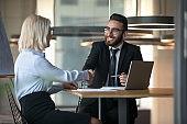 Middle eastern ethnicity HR manager hiring elderly woman people handshaking
