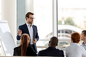Successful millennial businessman boss presenting new project to employees