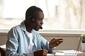 Happy focused african ethnic young guy attending online educational seminar.