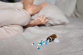 Depressed woman lying covering with pillow near pills on bed