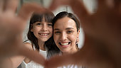 Close up portrait happy family of two making heart gesture.