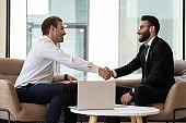 Smiling international businessmen handshake closing deal at meeting