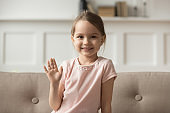 Headshot portrait little cheerful girl wave hand looking at camera