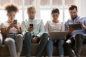 Concentrated diverse people sitting together on sofa, using different gadgets.