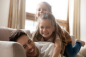 Funny little daughters playing with dad lying on his back