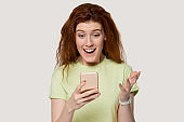 Surprised redhead girl use cellphone shocked by unexpected news
