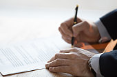 Close up view of male hand signing business contract concept