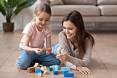 Smiling mom and little daughter playing with toy blocks