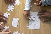 Top above close up view multiracial human hands assembling puzzle