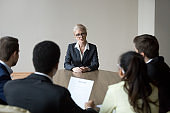 Middle-aged confident applicant talking to hr managers during job interview