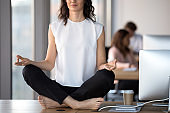 Barefoot businesswoman meditating sitting in lotus position on office table