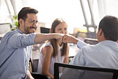 Colleagues fist bumping sitting on chairs at workplace
