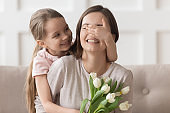 Cute little daughter cover mom eyes presenting flowers