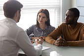 Young multiethnic couple consulting with male agent at office meeting