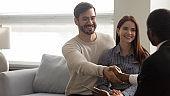 Happy Caucasian clients handshake male consultant greeting