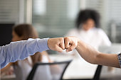 Close up of male colleagues give fists bump in office