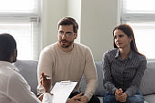 Clients couple talk consulting with male psychologist at meeting